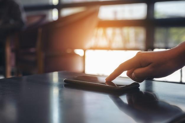 Een vinger aanraken en wijzen op mobiele telefoon op tafel