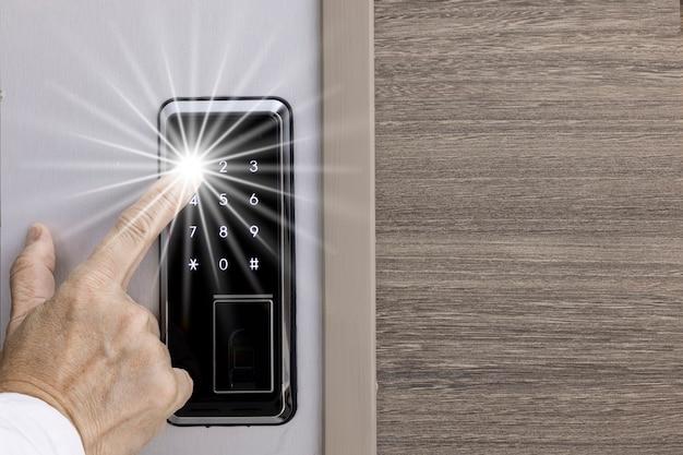 Een vinger die op het numerieke toetsenbord van het elektronische deurinvoersysteem drukt.