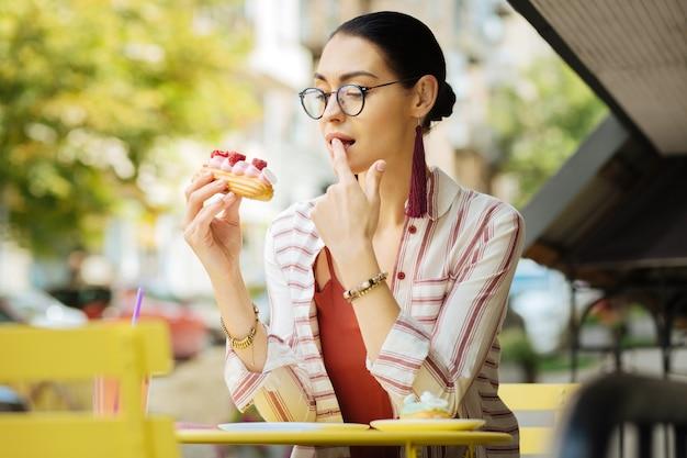Een vinger likken. jonge vrouw voelt zich onder de indruk en likt haar vinger tijdens het eten van heerlijke frambozen eclair in een café