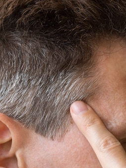 Een vinger wijst naar het grijze haar op zijn hoofd.