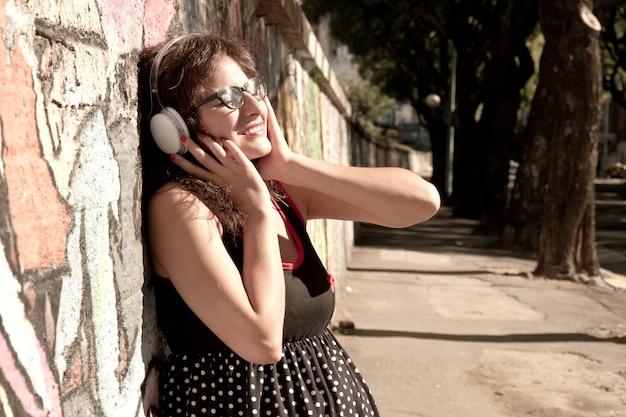 Een vintage gekleed meisje dat luistert naar muziek in een stedelijke omgeving.