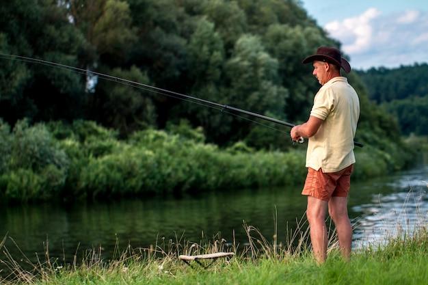 Een visser in korte broek, een hoed en een t-shirt vist aan de oever van het meer. vissen, hobby's, recreatie