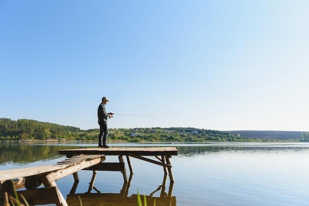 Een visser met een hengel aan de oever van de rivier