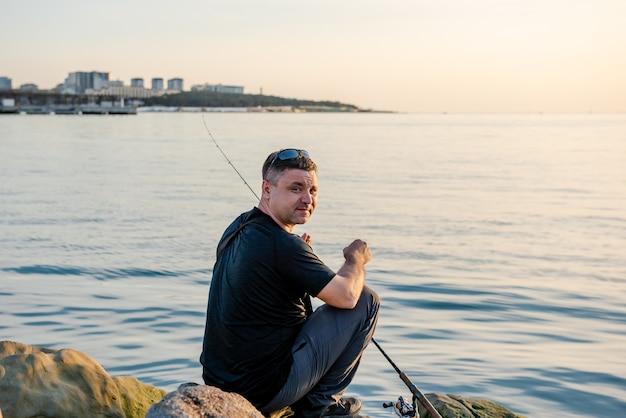 Een visser vangt vis in de zee met een hengel zittend op de kust van de rotsen bij zonsondergang