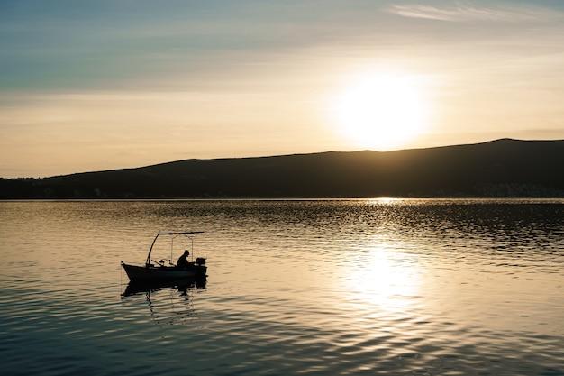 Een visser vangt vis in de zee tegen de achtergrond van een berg en zonsondergang.