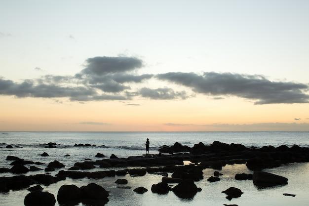 Een visser vist in de zwarte stenen in de oceaan.