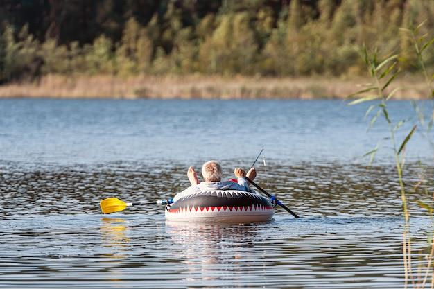 Een visser vist op hengels van een rubberboot met roeispanen, bos op een onscherpe achtergrond