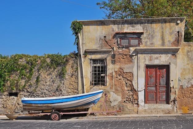 Een vissersboot op een kar dichtbij het oude huis. rhodos, griekenland