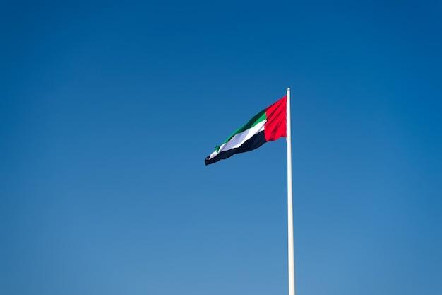 Een vlag van de verenigde arabische emiraten die tegen een schone en rustige hemel vliegt. de vae viert zijn nationale feestdag elk jaar op 2 december.