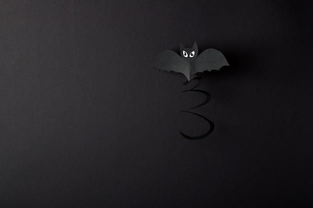 Een vleermuis op een zwarte achtergrond heeft een plek voor tekst. een wenskaart voor halloween. ambacht gemaakt van papier.