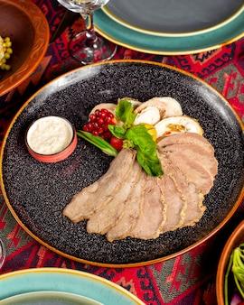 Een vleesschotel met plakjes vlees en paté gegarneerd met granaatappel en kruiden