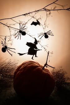 Een vliegend hekssilhouet van zwart document en spinnen en puppkin op oranje gradiënt