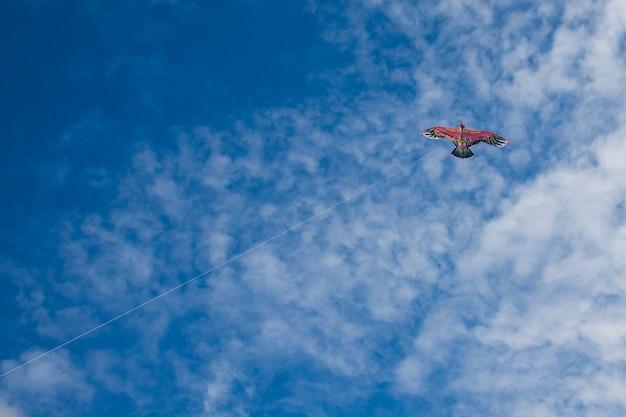 Een vlieger in de vorm van een vogel op de achtergrond van een blauwe lucht met wolken