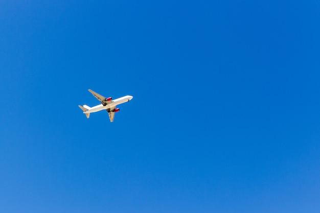 Een vliegtuig dat in de blauwe hemel zonder witte wolken vliegt