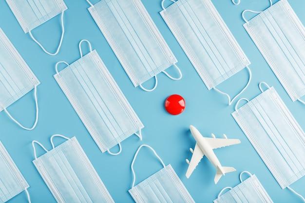 Een vliegtuig op een blauw oppervlak omringd door medische maskers met een rode bestemmingspunt