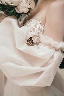 Een vlinder zit op een trouwjurk stijlvolle roze trouwjurk mooie bruiloft decor de bruid hol...