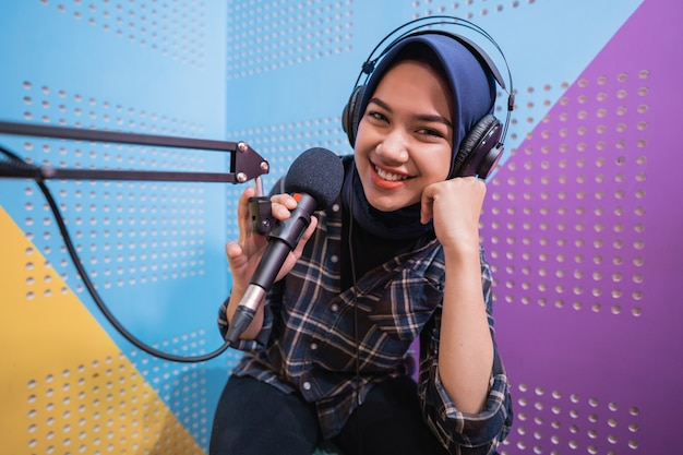 Een vloggermeisje neemt een podcast op in de studio