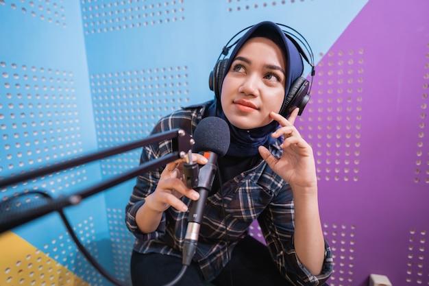 Een vloggermeisje neemt een podcast op in studiodenken