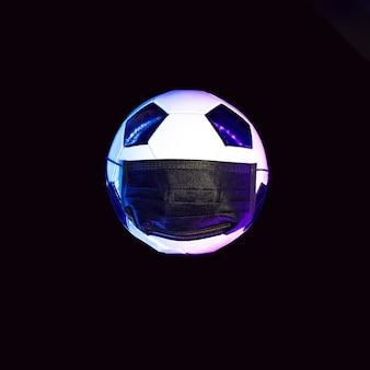 Een voetbal in een zwart medisch masker van het virus. in het licht van neon op een donkere muur