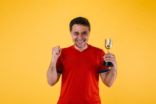 Een voetbalfan in een rode trui, hij balt zijn vuist en houdt een winnaarstrofee vast.