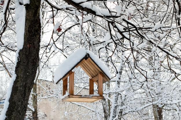 Een vogelvoederhuis aan een boom onder de sneeuw in de winter