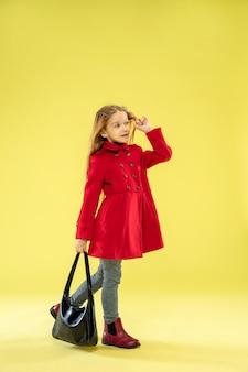 Een volledig lengteportret van een helder modieus kaukasisch meisje in een rode regenjas die een zwarte zak op geel houdt