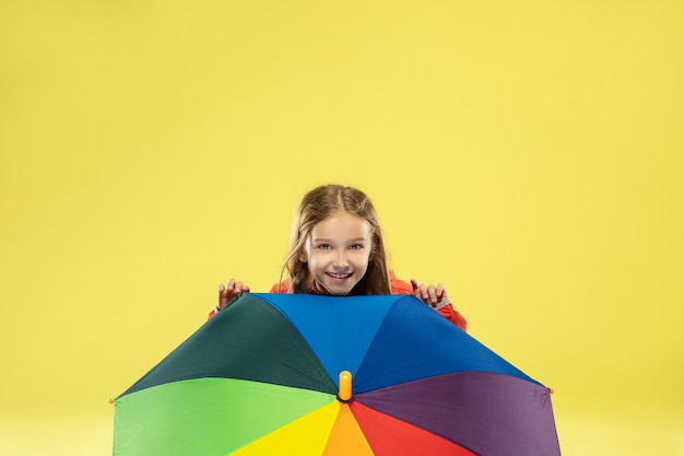 Een volledig lengteportret van een helder modieus meisje in een regenjas
