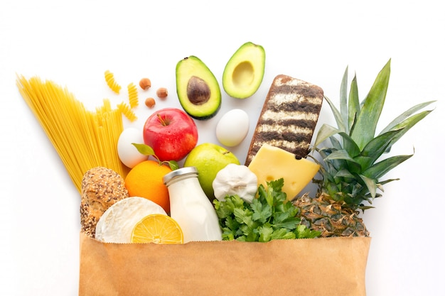 Een volledig papieren zak met verschillende gezonde producten. gezonde voeding achtergrond. supermarkt voedsel concept. melk, kaas, fruit, groenten, avocado's en spaghetti. winkelen bij de supermarkt. ingrediënten.