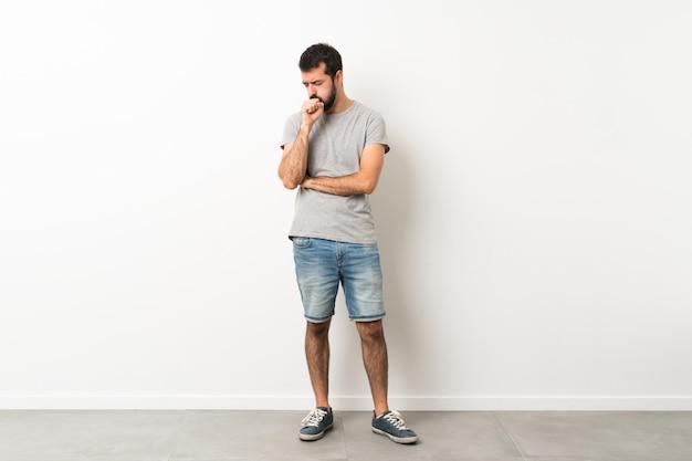 Een volledig shot van een knappe man met baard lijdt aan hoest en voelt zich slecht
