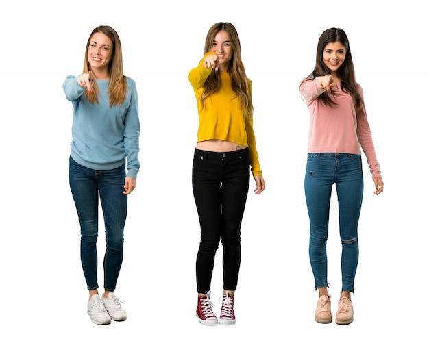 Een volledige foto van een groep mensen met kleurrijke kleding wijst naar je