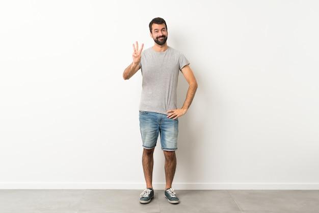 Een volledige lengte shot van knappe man met baard blij en drie tellen met vingers