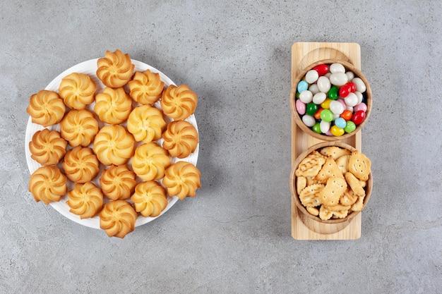Een volledige plaat van zelfgemaakte koekjes met twee kommen crackers en suikergoed op een dienblad op marmeren achtergrond. hoge kwaliteit foto