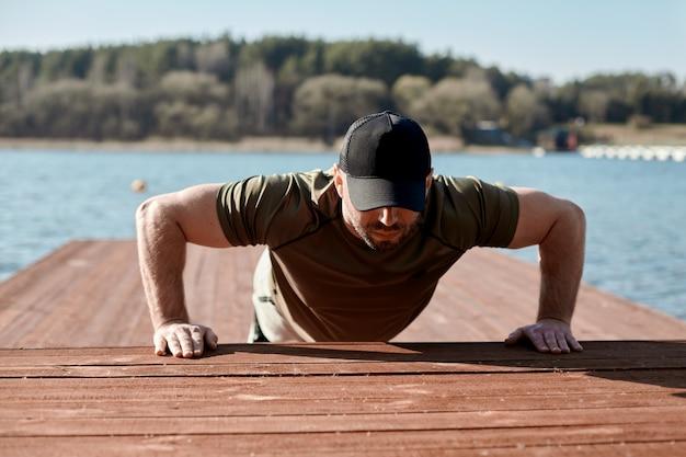 Een volwassen atletische man voert push-ups uit op een pier op het meer. een man houdt zich bezig met buitensporten. sport, fitness, lifestyle