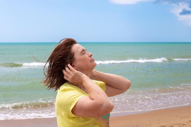 Een volwassen bejaarde vrouw aan de kust sloot haar ogen voor de zeebries. reizen en toerisme in de zomer.
