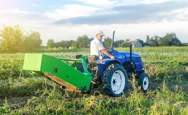 Een volwassen blanke boerenchauffeur op een landbouwtractor rijdt naar het veld om aardappelen te oogsten