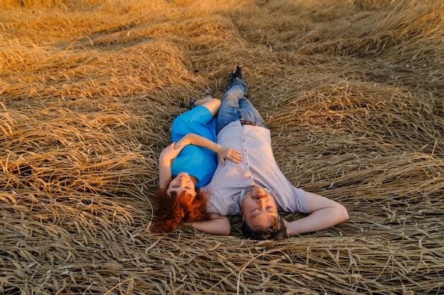 Een volwassen boer en zijn vrouw liggen op met regen bedekte tarwe. een schot genomen vanuit het bovenaanzicht.