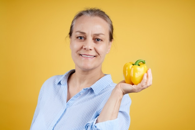 Een volwassen glimlachende huisvrouw in een wit en blauw overhemd heeft een gele paprika in haar hand