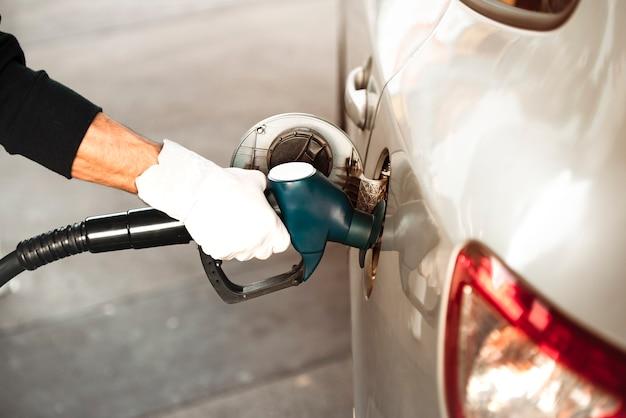Een volwassen hand die de benzinetank van de auto opnieuw vult met een pijp in een benzinestation