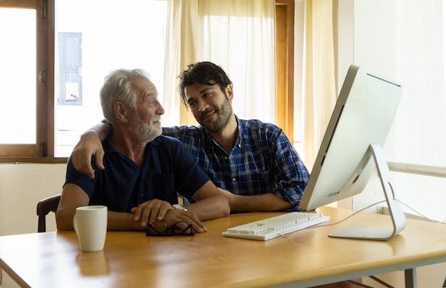 Een volwassen hipsterzoon en een oudere vader brengen thuis tijd samen door met praten, zorg voor vader