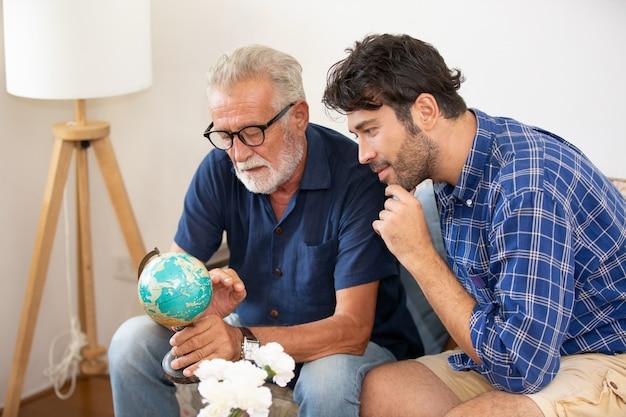 Een volwassen hipsterzoon en senior vader brengen samen tijd door thuis, praten, zorgen vader