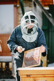 Een volwassen imker werkt aan een bijenkorf in de buurt van de bijenkorven. natuurlijke honing rechtstreeks uit de korf.
