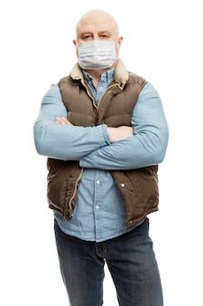 Een volwassen kale man met een medisch masker staat met zijn armen over elkaar op zijn borst. de financiële crisis en quarantaine tijdens de pandemie van het coronavirus. voorzorgsmaatregelen. geïsoleerd op een witte.