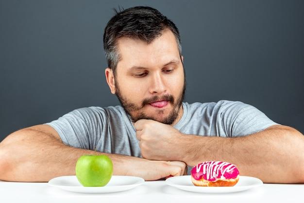 Een volwassen man kiest tussen een donut en een groene appel. concept weerstand tegen verleiding, fast food, gezonde voeding, voeding, lichaamsverzorging.