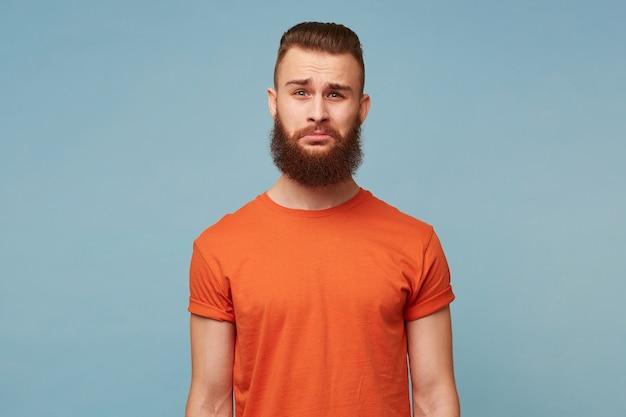 Een volwassen man met een dikke baard, gekleed in een rood t-shirt geïsoleerd op blauw