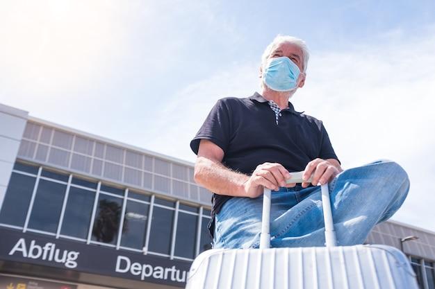 Een volwassen man met een medisch masker met zijn bagage of trolley die reist en vluchten neemt op de luchthaven - senior wacht op zijn vlucht om coronavirus of een ander type virus te voorkomen (covd-19)