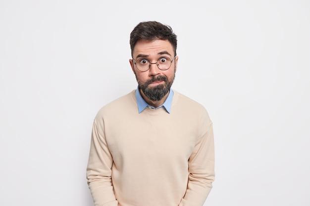 Een volwassen man met een verbaasde baard tuit zijn lippen, draagt een ronde optische bril en een casual nette trui