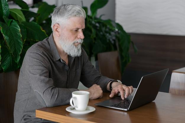 Een volwassen man met grijs haar en een baard werkt op zijn laptop in zijn kantoor of wachtruimte op de luchthaven