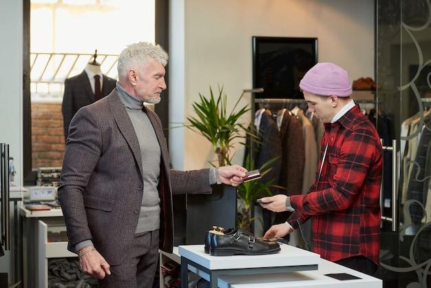 Een volwassen man met grijs haar en een sportieve lichaamsbouw geeft een creditcard aan een verkoper om aankopen in een kledingwinkel te betalen. een mannelijke klant met een baard en een winkelbediende in een boetiek.
