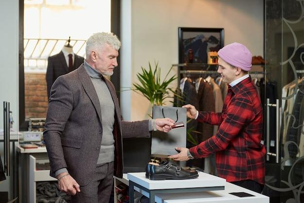 Een volwassen man met grijs haar en een sportieve lichaamsbouw geeft een creditcard aan een verkoper om een aankoop in een kledingwinkel te betalen. een winkelbediende geeft een papieren zak aan een mannelijke klant met een baard