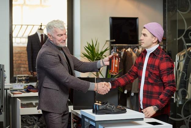 Een volwassen man met grijs haar en een sportieve lichaamsbouw geeft een fles whisky aan een verkoper in een kledingwinkel. een mannelijke klant met een baard en een winkelbediende in een boetiek.